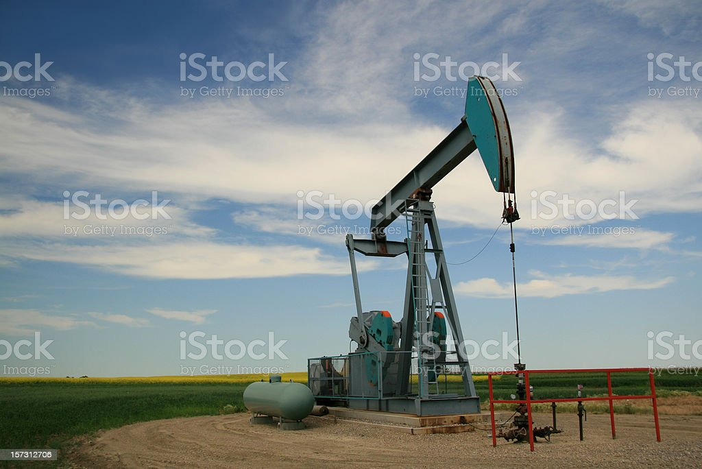 Blue pump jack on farm pumping for oil. royalty-free stock photo