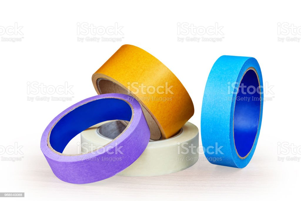 Blue, purple and yellow rollers of adhesive tape on white. stock photo