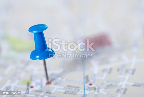 Pushpin marking a location on a city map.