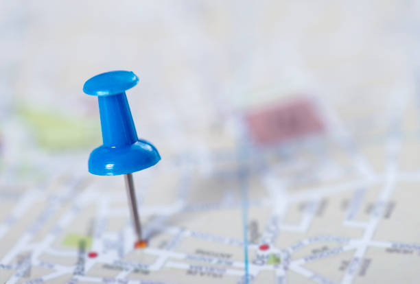 Blue push pin stuck in a street map stock photo