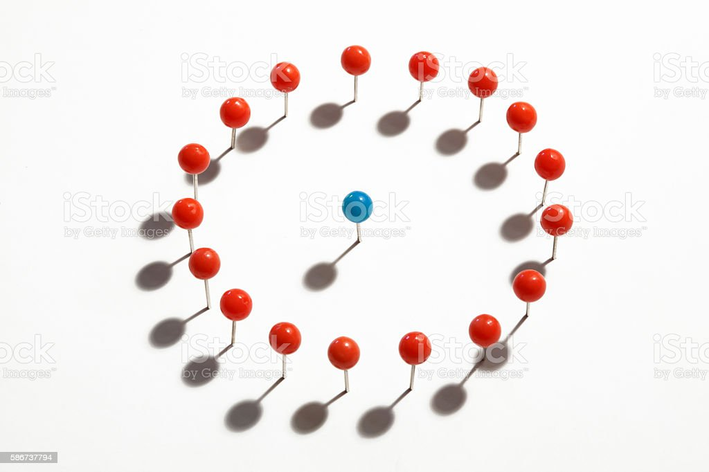 Blue Push Pin Surrounded By Circle Of Red Push Pins stock photo