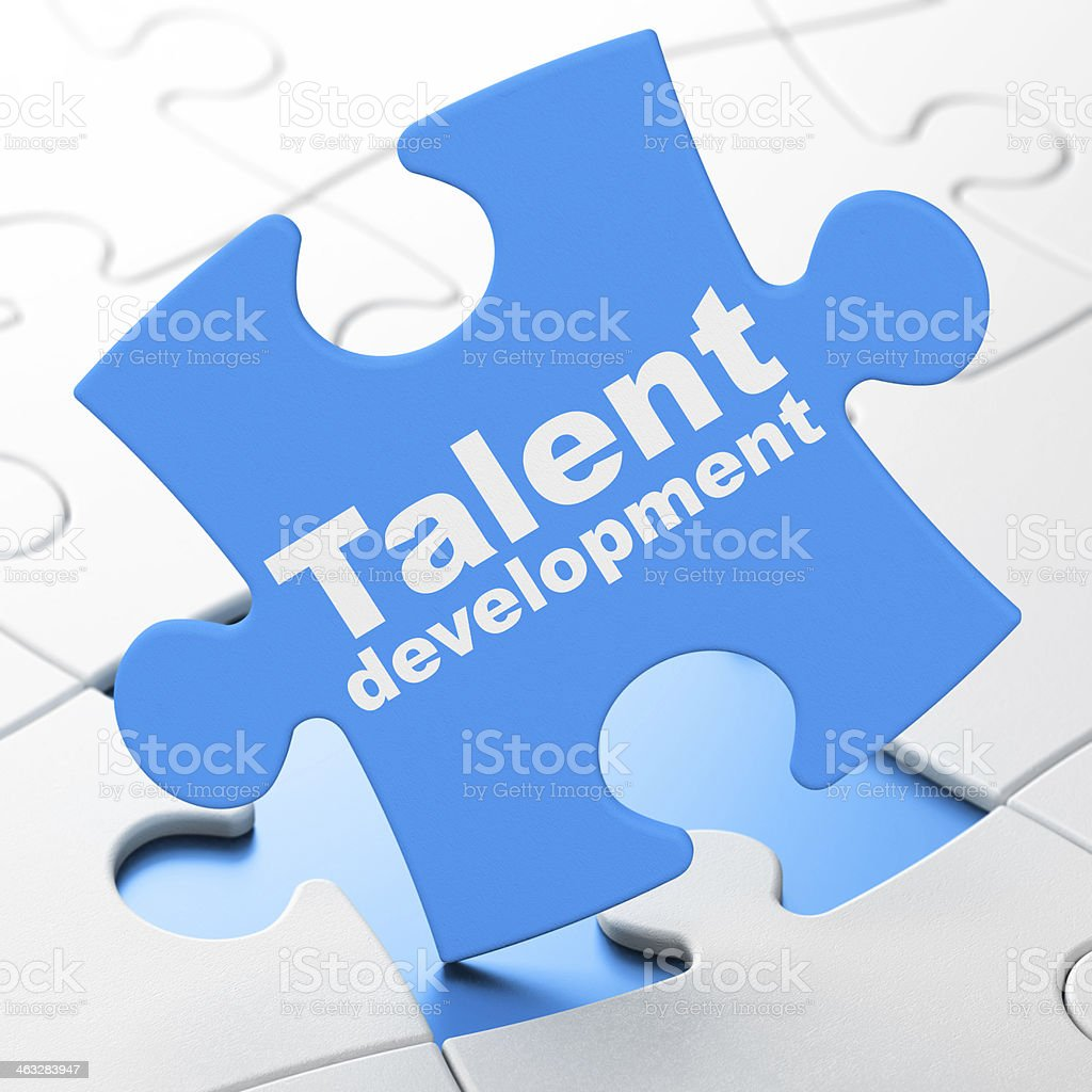 Blue puzzle piece with the words talent development on it royalty-free stock photo