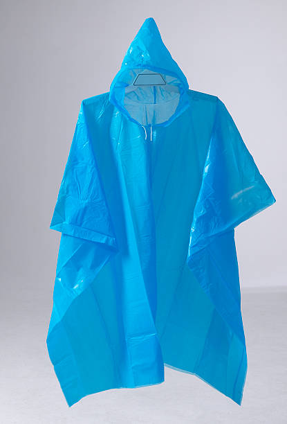Blue rain poncho hanging Blue rain poncho hanging on grey background waterproof clothing stock pictures, royalty-free photos & images
