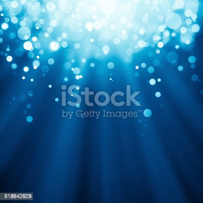 istock Blue rays of light with bubbles and glitters 518642629