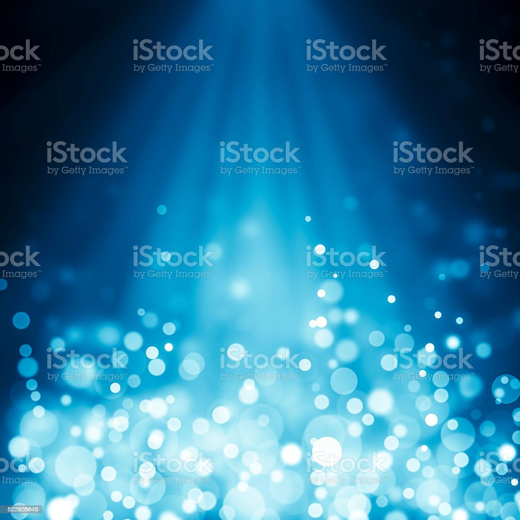 Blue rays of light with bubbles and glitters stock photo
