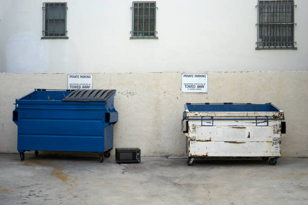 blue recycling and white trash bins in an alley stock photo