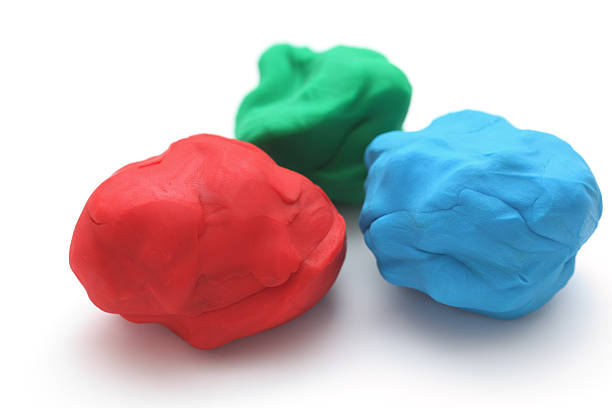 Blue, red and green moulds of plasticine n a white surface