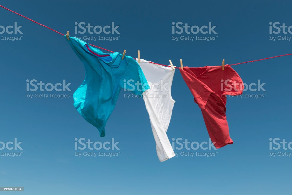 Blue, Red, White T-shirts blowing on a washing line. stock photo