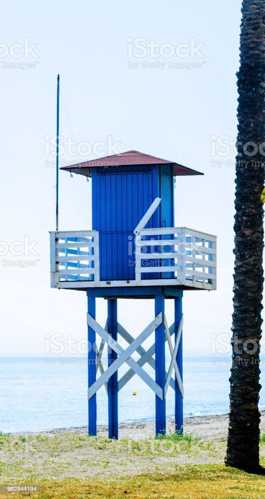 Cabana de resgate azul em uma praia arenosa, segura relaxar pelo oceano, um belo dia de sol - Foto de stock de Areia royalty-free
