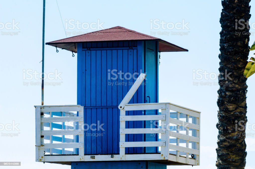 Blue rescue hut on a sandy beach, safe relax by the ocean, a beautiful sunny day - Royalty-free Assistance Stock Photo