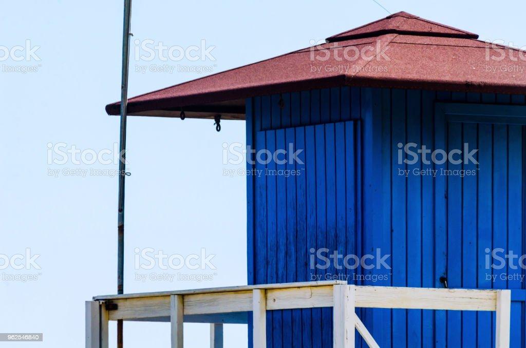 Cabana de resgate azul em uma praia arenosa, segura relaxar à beira-mar - Foto de stock de Areia royalty-free