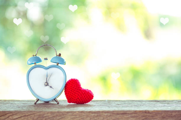 blue retro heart shape clock with red heart  knitting shape on wooden mock up over blurred green garden on day noon light stock photo