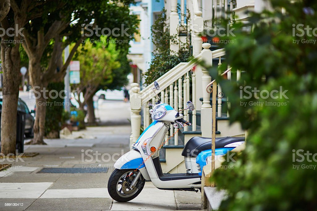 Blue retro scooter parked on a street of San Francisco stock photo