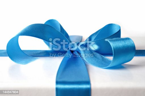istock Blue ribbon beautifully tied on a white package  144347604