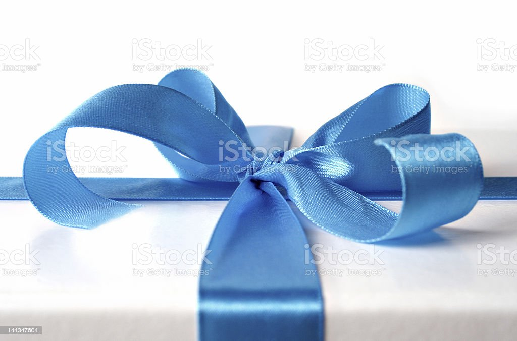 Blue ribbon beautifully tied on a white package  stock photo