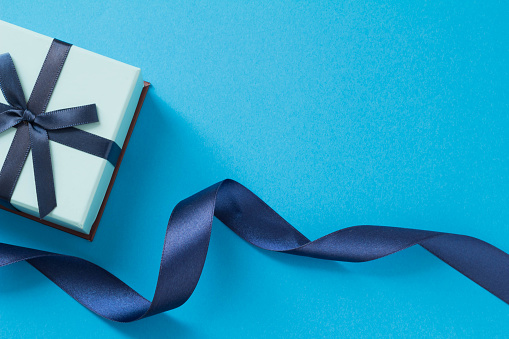 It is an image of a gift that consists of a blue ribbon and a blue solid background.