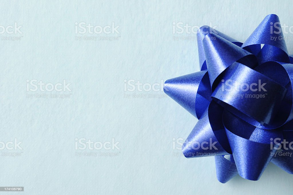 Blue ribbon on blue wrapping paper with copy space royalty-free stock photo