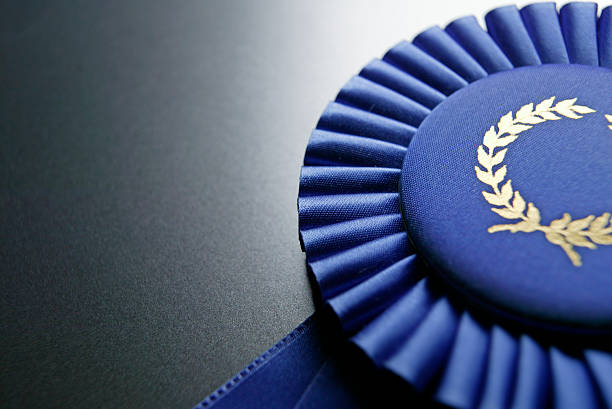 blue ribbon rosette on dark gray graduated background - award stock photos and pictures