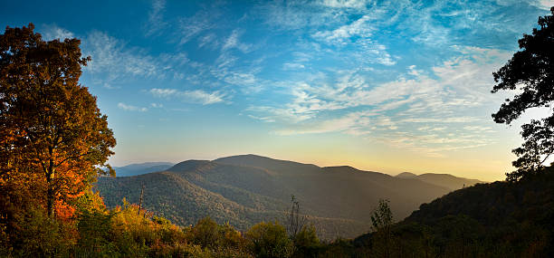 Blue Ridge Mountains in Autumn Panorama The early morning Autumn sun breaks over the mountains in Shenandoah National Park bringing out the brilliant reds and oranges of the deciduous trees. blue ridge mountains stock pictures, royalty-free photos & images