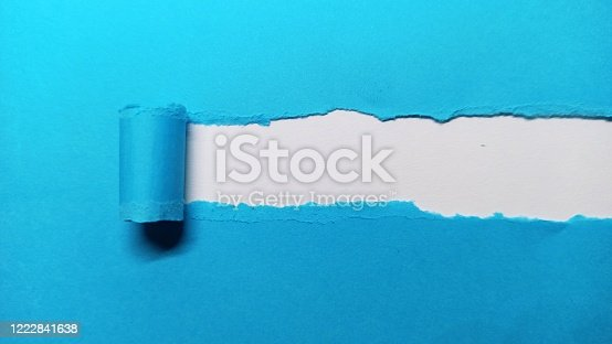 istock Blue ripped paper curled up template on white background 1222841638