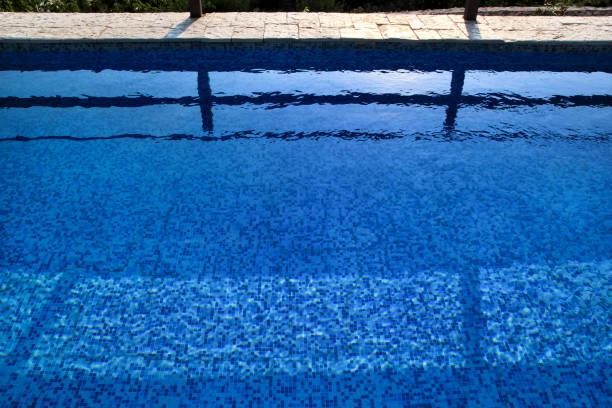 Água rasgada azul na piscina no recurso tropical com borda do pavimento. Parte do fundo da parte inferior da piscina. Luz azul claro ondulações da água da associação com reflexão do sol. Superfície da piscina. - foto de acervo