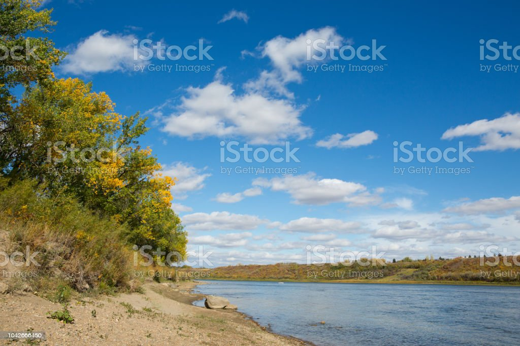Blue river with trees on sandy bank in autumn with blue sky and clouds stock photo