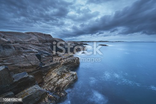 A wide angle view of ominous clouds over a rugged rocky coastline.