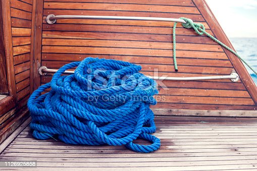 Blue rope on a ship on a wooden table.