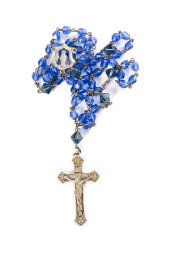Blue beaded rosary on a white background