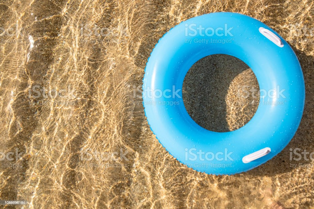 Blue rubber ring floating on shallow clear sea at the shoreline of Pedn Vounder Beach, Cornwall on a bright sunny day. stock photo