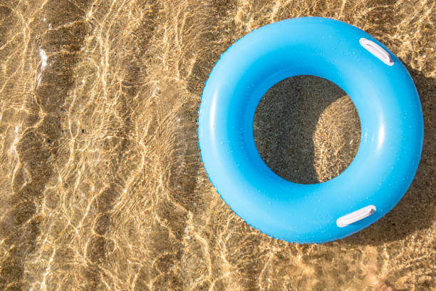 blue rubber ring floating on shallow clear sea at the shoreline of pedn vounder beach, cornwall on a bright sunny day. - rubber ring stock pictures, royalty-free photos & images