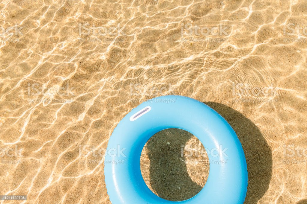 Blue rubber ring floating on the clear shallow sea at Pedn Vounder Beach, Cornwall stock photo
