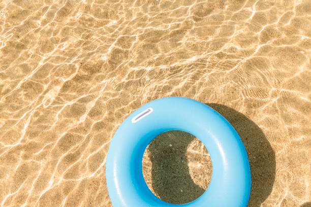 blue rubber ring floating on the clear shallow sea at pedn vounder beach, cornwall - rubber ring stock pictures, royalty-free photos & images