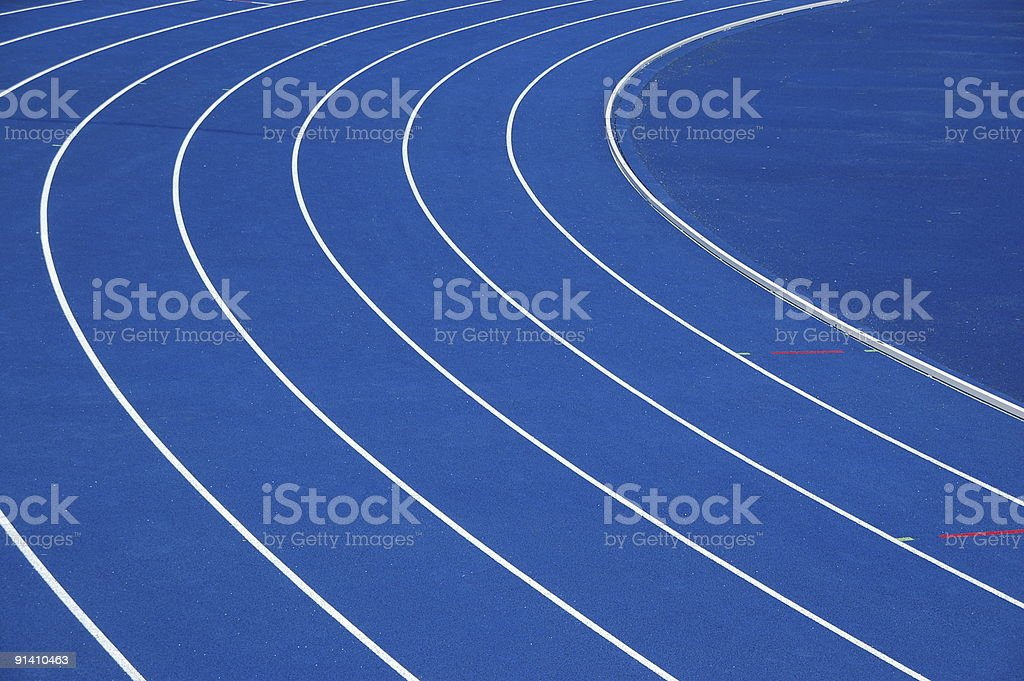 Blue running track with white lines royalty-free stock photo