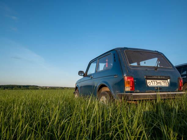 blaurussischer geländewagen lada niva 4x4 (vaz 2121 / 21214) auf dem feld geparkt. - lada niva stock-fotos und bilder