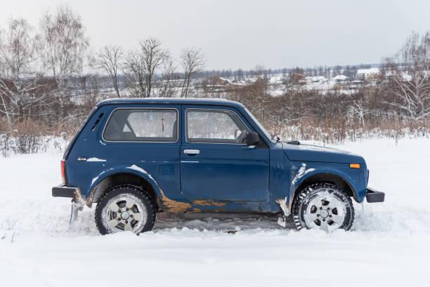 blaue russischer geländewagen lada niva 4 x 4 (vaz 2121 / 21214) auf das schneefeld geparkt. - lada niva stock-fotos und bilder