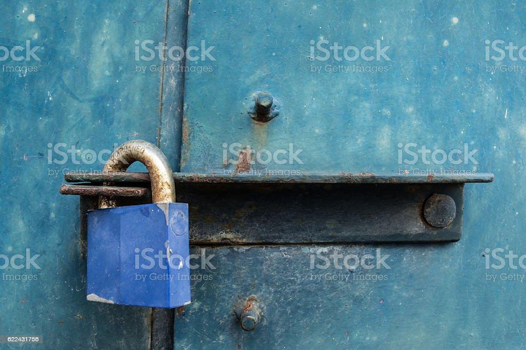 Blue rusty padlock on steel door. stock photo