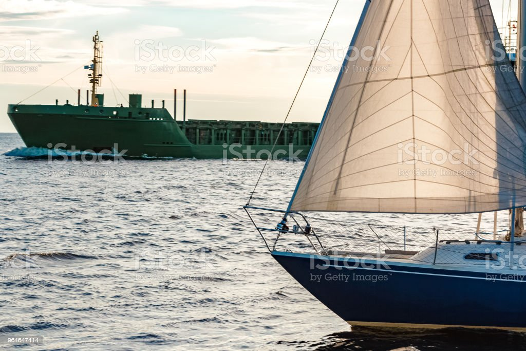 Blue sailboat against cargo ship royalty-free stock photo