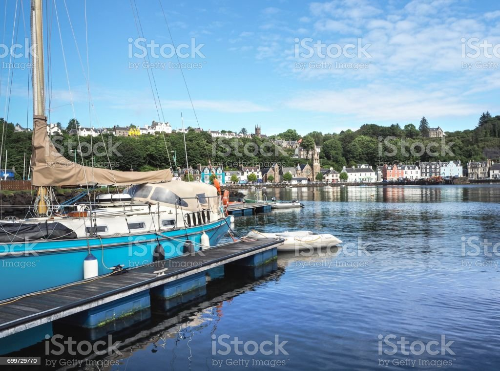 Blue Sailboat On Tobermory Town Background stock photo