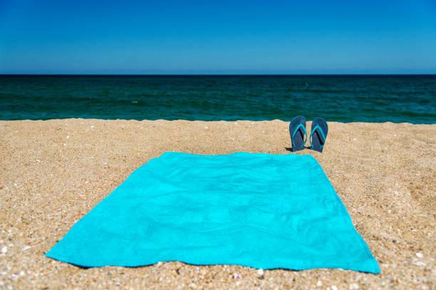 Blaue Sandale Flip Flop und Handtuch auf gelbem sand – Foto
