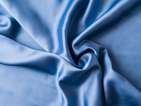 Indigo blue satin texture flowing fabric background with waves and crease