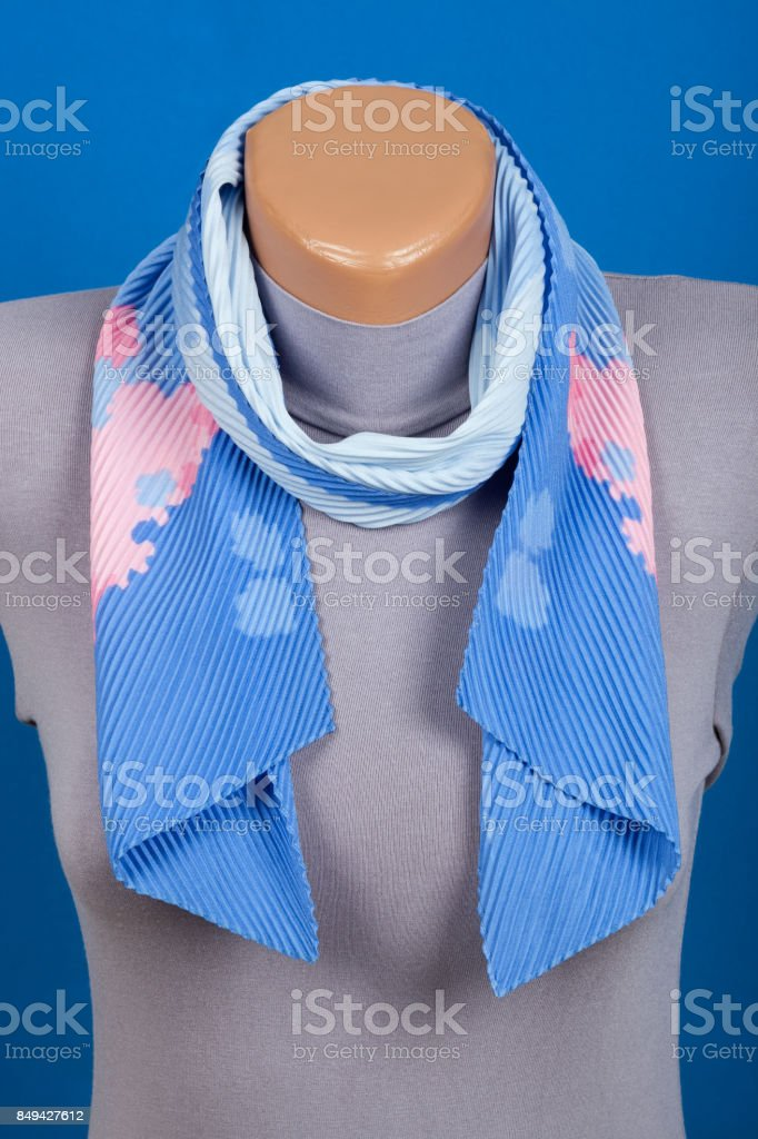 Blue scarf on mannequin isolated on blue background. stock photo