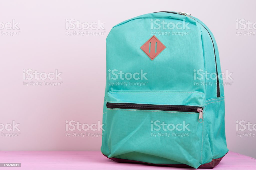 Blue school backpack is on a pink wooden table on pink background стоковое фото