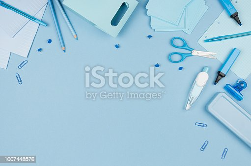 Blue school stationery top view as decorative border on soft pastel background, top view, horizontal.