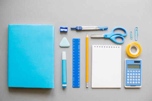 Blue school supplies on grey background stock photo