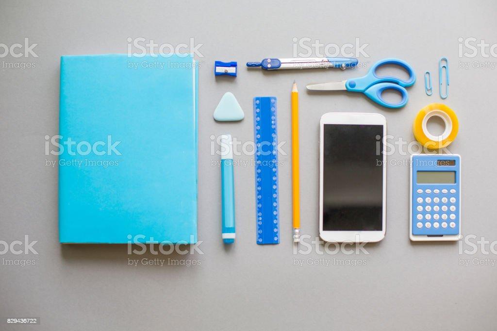 Blue school supplies on grey background stock photo