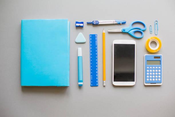 blaue schulmaterial auf grauem hintergrund - mittelschule bücher stock-fotos und bilder