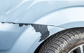 istock Blue scratched car with damaged and peeled paint in crash accident or parking lot and dented damage of metal body from collision 1128971523
