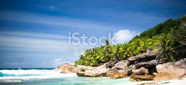 Blue sea and exclusive remote beach in Seychelles islands (La Digue) with turquoise water, coconut palm tree, granite rock