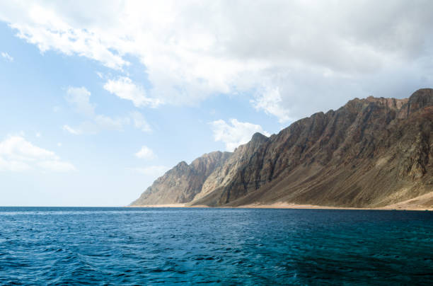 blue sea and high rocky mountains against the sky and clouds in Egypt Dahab South Sinai stock photo